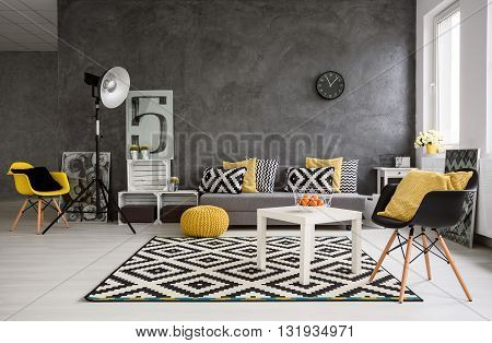 Stylish spacious living room with grey walls and black white and yellow decorations