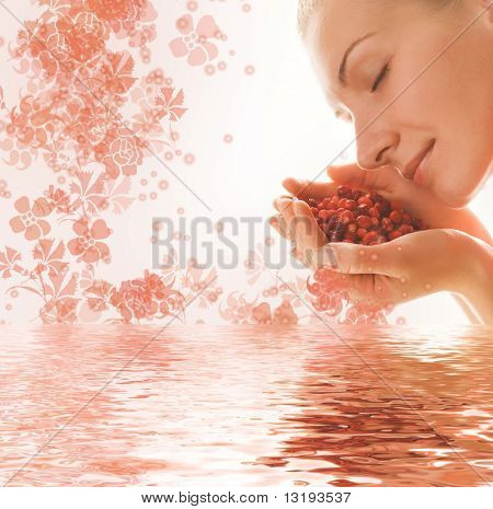 Beautiful young woman with a hanful of aromatic berries reflected in rendered water