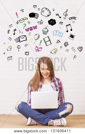 young woman sitting on wooden floor against concrete wall and using laptop