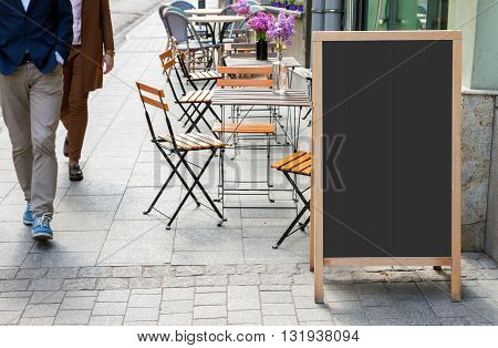 Blank menu blackboard on the street with cafe chairs and people passing by