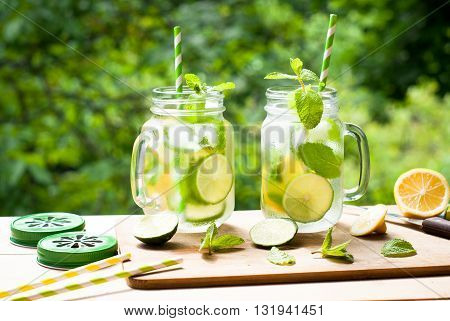 Summer drink lemonade mojito with lime lemon and mint in mason jar outdoor.