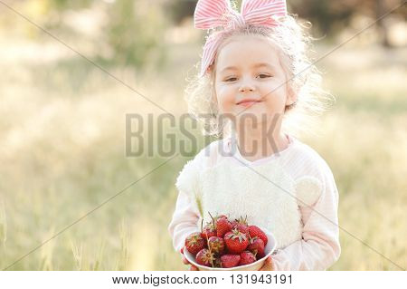 Smiling baby girl 4-5 year old holding bowl with berries outdoors. Looking at camera.