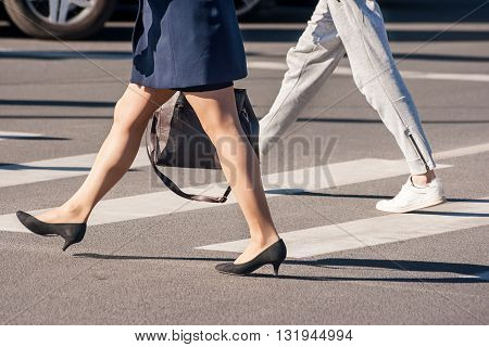 two pedestrians walking on a pedestrian crossing closeup