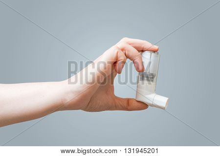 Hand holds inhaler for asthmatics. Healthcare concept