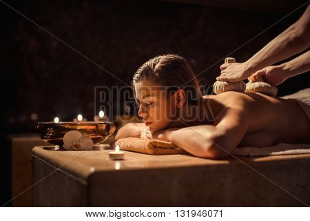 Woman with herbal compress massage in beauty spa