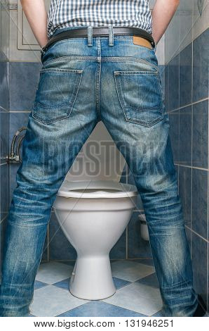 Man Peeing To Toilet Bowl In Restroom From Back.