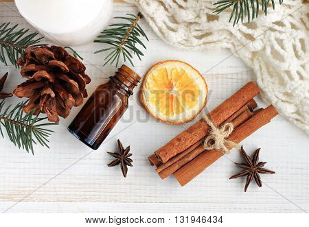 Winter home fragrances blend. Essential oils, orange, cinnamon sticks, anise, fir, cones, woolen blanket, top view.