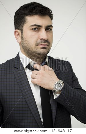Man fixing his tie. Professional businessman in a white background.