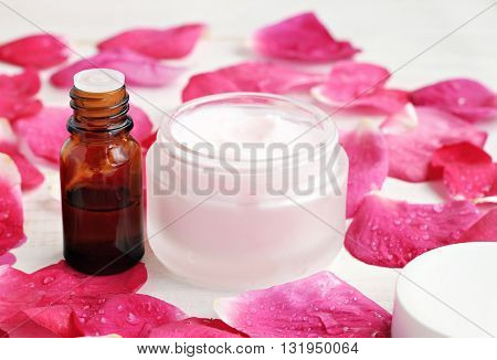 Jar of soft pinkish skin care cream, fragrance, bright pink fresh rose petals moistuned. Gorgeous aroma body care spa.