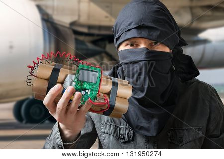Terrorism Concept. Terrorist In Airport Holds Dynamite Bomb In H