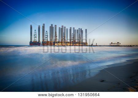 beach waves with oil platform in ocean. Caspian sea offshore oil rig drilling platform off the Baku, Azerbaijan.