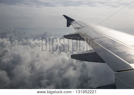 Plane flying over the clouds. Plane take off. View from the window. Jet plane take off at dusk. SUN ascending from behind the horizon.