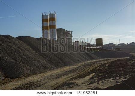 Quarry crusher plant in sand and gravel production. Cement production factory on mining quarry. Conveyor belt of heavy machinery loads stones and gravel. Construction works, machinery factory