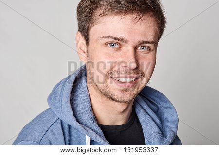 Handsome young man with light beard in blue hoodie