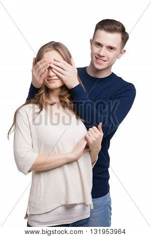 Portrait of smiling boyfriend covering his girlfriend's eyes.Isolated