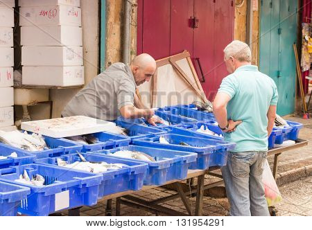 Acre Israel - 28 May 2016: Fresh fish merchant services buyer in market in the old city of Acre Israel