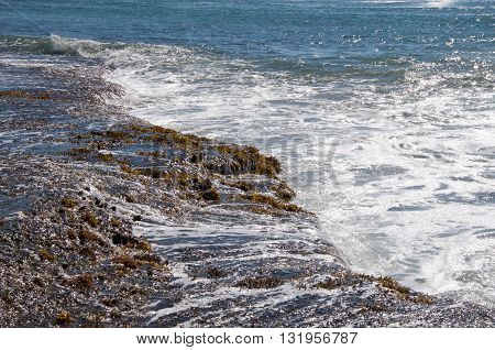 Waves rushing over the rocky beach reef in the Indian Ocean on the coral coast at Jake's Point in Kalbarri, Western Australia.