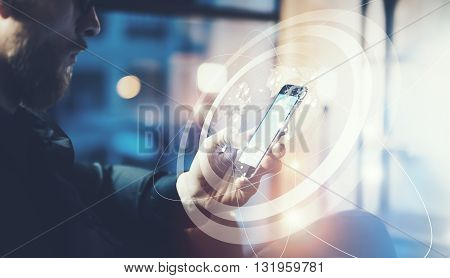 Picture businessman relaxing modern loft office.Man sitting in chair at night.Using contemporary smartphone, blurred background. Digital Connections World Wide Interfaces.Horizontal, film effect