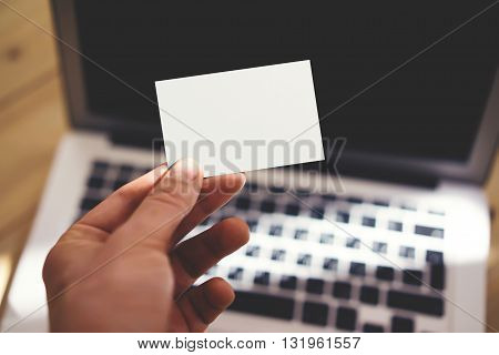 Photo Man Showing Blank White Business Card and Using Modern Laptop Blurred Background. Mockup Ready for Private Information. Sunlight Reflections Surface Gadget. Horizontal mockup