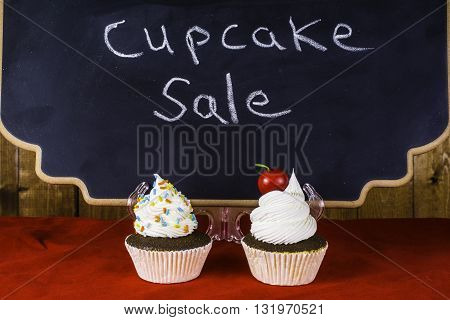 two cupcakes on red in front of chalkboard advertising cupcake sale with wood background