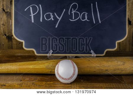 baseball bat and ball in front of chalkboard advertising play ball on wood background