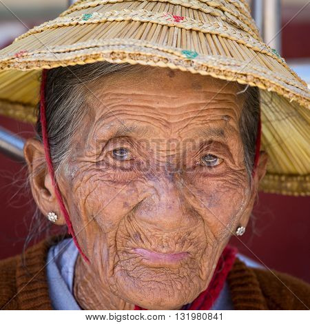 INLE LAKE MYANMAR - JANUARY 14 2016: Unidentified old woman in a straw hat . The local people are hospitable and friendly to tourists