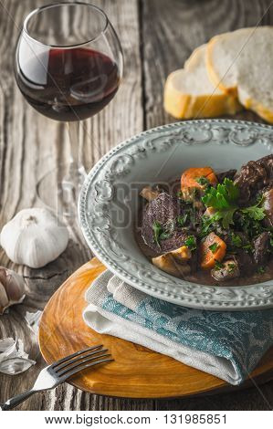 Beef bourguignon in a ceramic plate with a glass of wine vertical