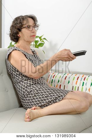 a middle-aged woman with a tv remote control