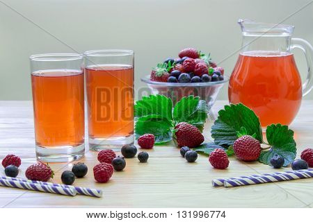 Left two glasses of berries compote near bowl with berries carafe compote on a light wooden background scattered berries straws and empty space. Fresh berries compote and empty space. Horizontal.