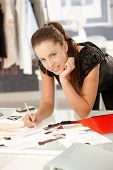 Young, attractive fashion designer working in office, drawing, leaning on desk, smiling.? poster
