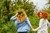 Best friends forever. Girlfriends strolling hand in hand. BFF. Walk. The girl on a head a wreath of wildflowers. Go away. poster