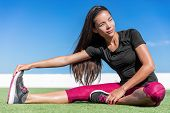 Fitness woman stretching one leg toe-touch stretch exercising hamstring and glute muscles stretches. Sporty Asian athlete exercising sitting forward bend legs exercise on grass in sunny outdoor gym. poster
