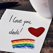 closeup of a red heart and the sentence I love you dads written in a note, which has a rainbow flag painted in it, placed on a dark wooden table next to a cup with coffee or tea poster