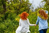 Best friends forever. Girlfriends strolling hand in hand. BFF. Walk. The girl on a head a wreath of wildflowers. Photos from behind. People are not recognizable poster