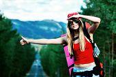 Pretty young woman tourist hitchhiking along a road.