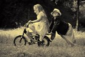 Cute children  is riding a bike in a summer park. Retro style.