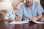 Senior couple signing will documents. Elderly caucasian man and woman sitting at home and signing some paperwork focus on hands. poster