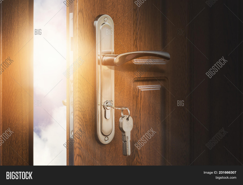 Half Open Door With Keys In Keyhole. Doorway To Heaven And Success.  Entrance Or