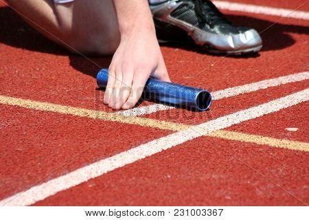Runner In The Starting Blocks With Baton