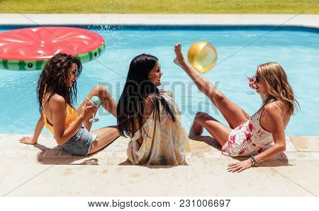 Party At Swimming Pool. Group Of Cheerful Girls At The Edge Of The Swimming Pool Drinking Cocktails