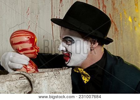 Scary evil clown playing with bloody doll