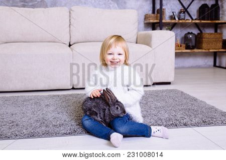 Cute Little Girl With Grey Easter Rabbit, Bunny. Blonde Baby Girl Smiling In White Sweater And Blue