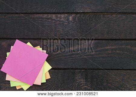 Stack Of Color Stickers On Dark Wooden Table.