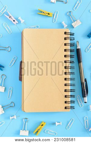 Open Notebook On A Light Blue Background. Stationery Is In Disarray. Beautiful Bright Background Wit