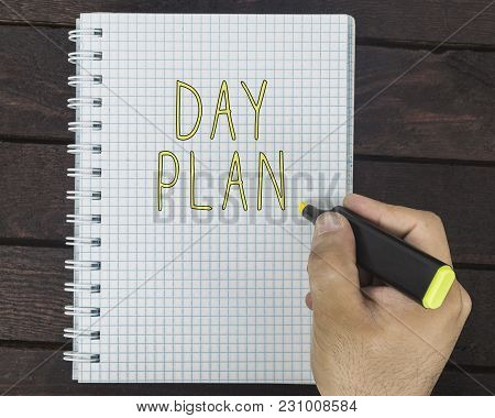 Male Hand Is Writing Day Plan On A Notepad On A Wooden Table
