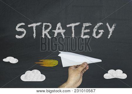 Strategy Inscription On A Black Chalkboard. Paper Plane