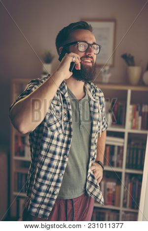 Cheerful Young Man Having Phone Conversation On His Smart Phone