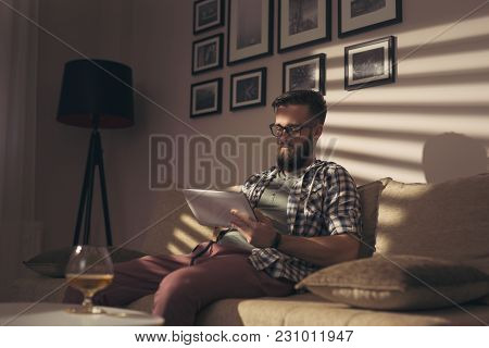 Handsome Young Man Sitting On A Living Room Sofa, Working On A Tablet Computer