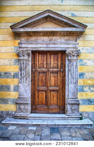 Medieval Ancient Wooden Door With Ornate Stone Columns, Italy. Front View, Facade With Yellow And Gr