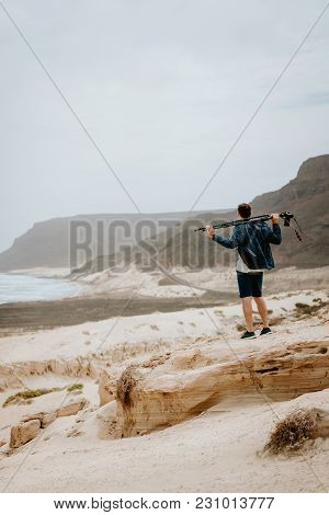 Photographer With Camera Looking For Motive Of Unique Landscape. Sand Dunes And Volcanic Cliffs On T